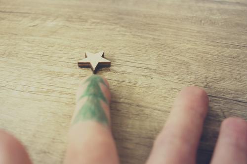 Weihnachtsdekoration mit kleinem Stern und einem auf einem Finger gemalten Tannenbaum auf einem Untergrund aus Holz Feste & Feiern Weihnachten & Advent Hand