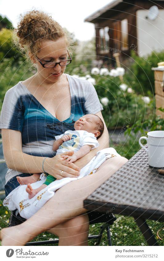 kaukasische Mutter mit ihrem Neugeborenen, die draußen in ihrem Garten sitzt Zuneigung Baby schön blond Bonden Pflege Kaukasier Stuhl Kind Kindheit niedlich