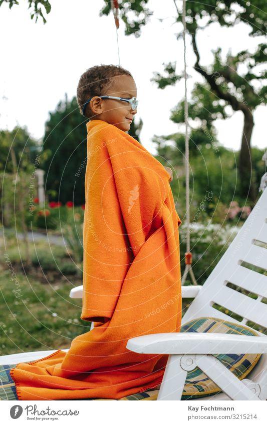 Seitenansicht eines farbigen Jungen, der mit einer orangefarbenen Decke bedeckt ist und lächelt Afroamerikaner schön schwarz Schwarze sorgenfrei nachlässig