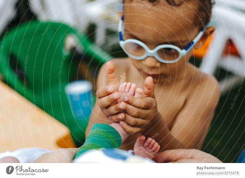 kleiner farbiger Junge erkundet die Füße seines kleinen Brüderchens Zuneigung schön Bonden Hermandad Pflege fürsorglich Kind Kindheit bunt niedlich erkundend