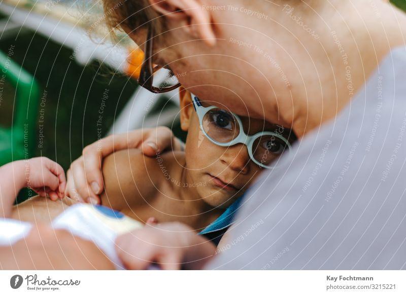 kleiner farbiger Junge, der in den Armen seiner Mutter Trost sucht Zuneigung ängstlich schön Bonden Pflege fürsorglich Kaukasier Kind Kindheit Komfort betroffen