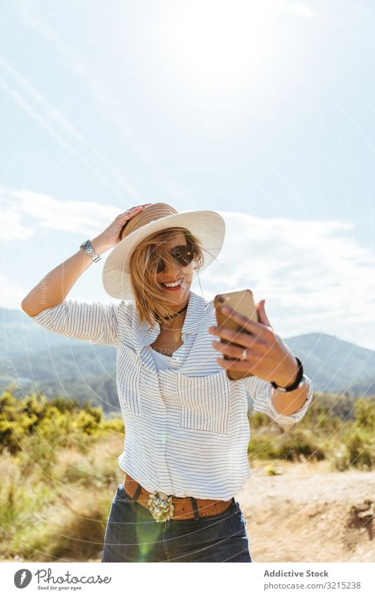 Junges Mädchen lächelt beim Blick auf ihr Smartphone Frau Glück Telefon Sonnenuntergang benutzend Menschen Mobile Hut Sonnenbrille jung klug Kaukasier Person
