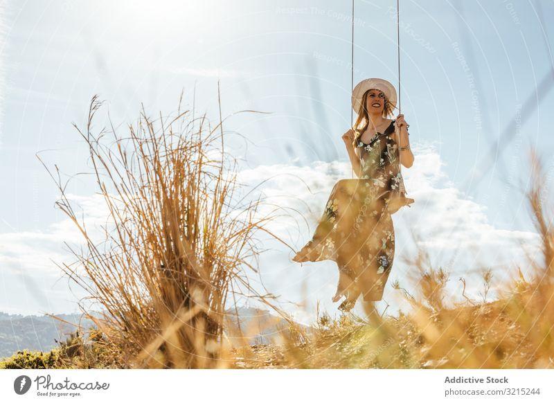 Glückliches Mädchen genießt auf einer Schaukel bei Sonnenuntergang pendeln Frau Fröhlichkeit Natur schön Silhouette jung Lifestyle Urlaub Landschaft Sommer