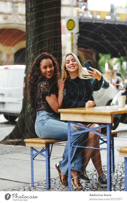 Freunde nehmen Selbstgefälligkeit in Straßencafé Frau Café reden Berlin schön Lächeln Glück Zusammensein Freizeit Genuss Restaurant rassenübergreifend hübsch