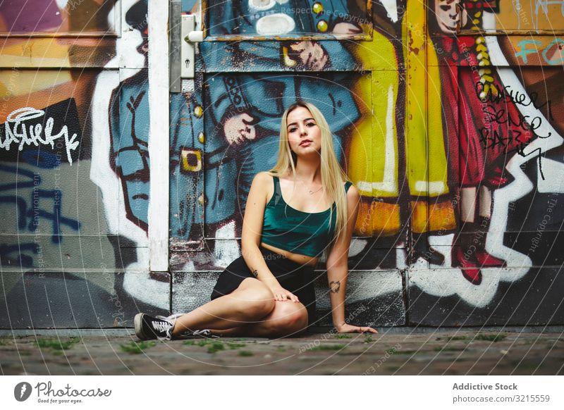 Stilvolle Frau mit Sonnenbrille posiert an Graffiti-Wand auf Stadtstraße. stylisch Straße urban posierend Sitzen Porträt attraktiv Schönheit trendy Lifestyle
