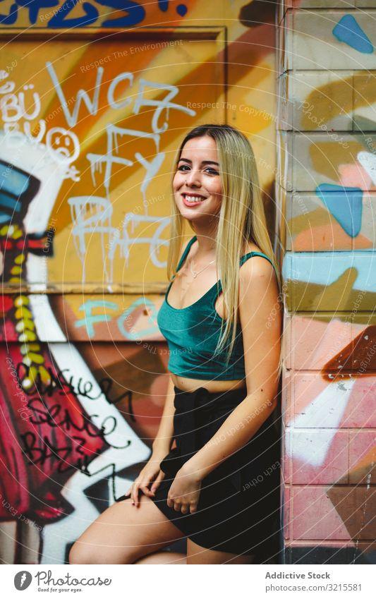 Stilvolle Frau mit Sonnenbrille posiert an Graffiti-Wand auf Stadtstraße. stylisch Straße urban posierend Porträt attraktiv Schönheit trendy Lifestyle hübsch