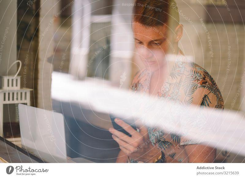 Mann spricht auf Smartphone, während er auf dem Laptop surft sprechend freiberuflich Browsen konzentriert fokussiert nachdenklich benutzend Sprechen Glas Beruf