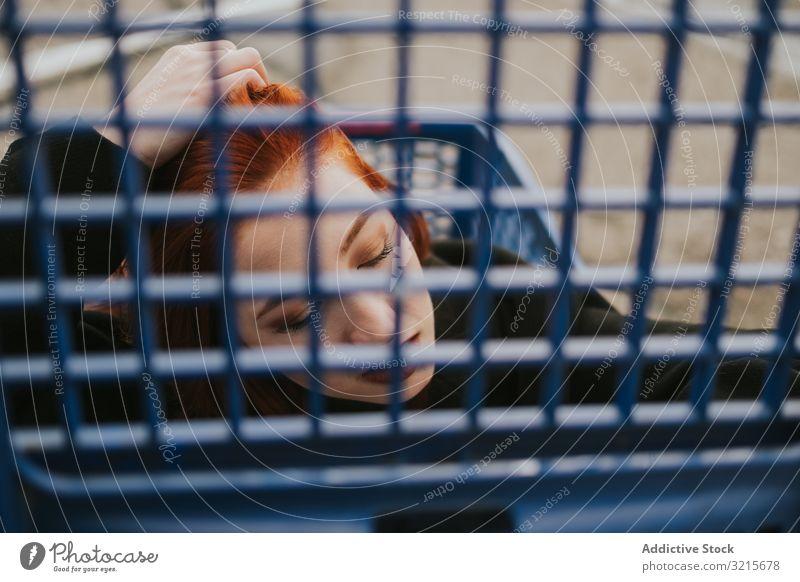 Frau schaut durch das Einkaufswagengitter im Einkaufswagen attraktiv jung schön lässig klug Handwagen modern Freude Rotschopf hübsch Vergnügen stylisch kaufen