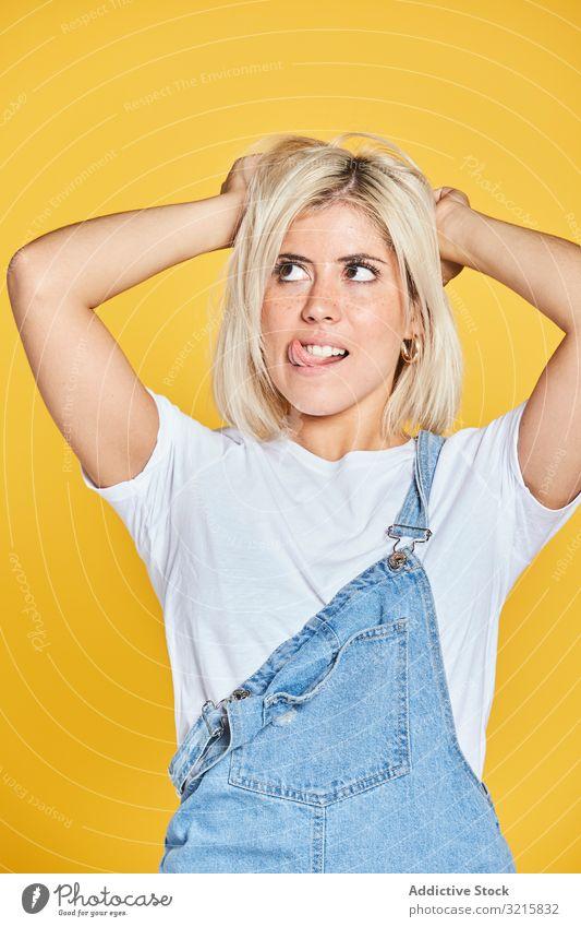 Trendige blonde Frau im Denim-Sonnenkleid modisch stylisch glamourös trendy Jeanshose Jeansstoff jung Person schön attraktiv hübsch schlank nachdenklich