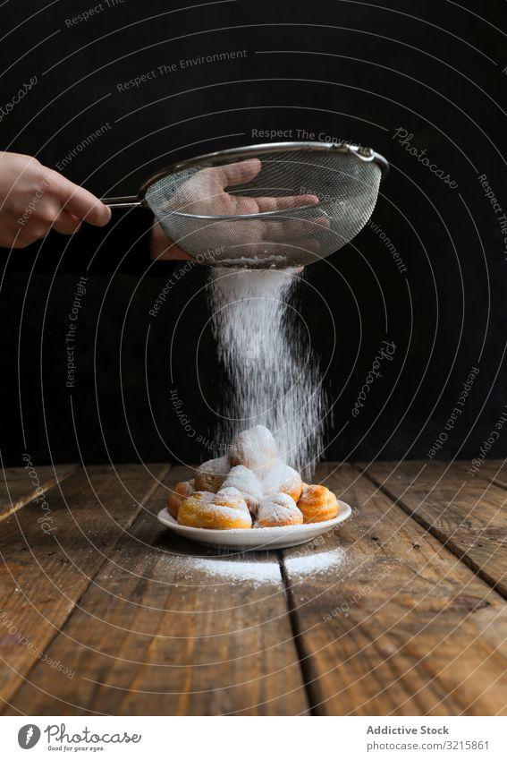 Person, die Kekse mit Puderzucker bestreut Zucker bestäuben Lebensmittel Biskuit Gebäck Sieb selbstgemacht Zuckerguß Küchenchef süß lecker Pulver Bäckerei