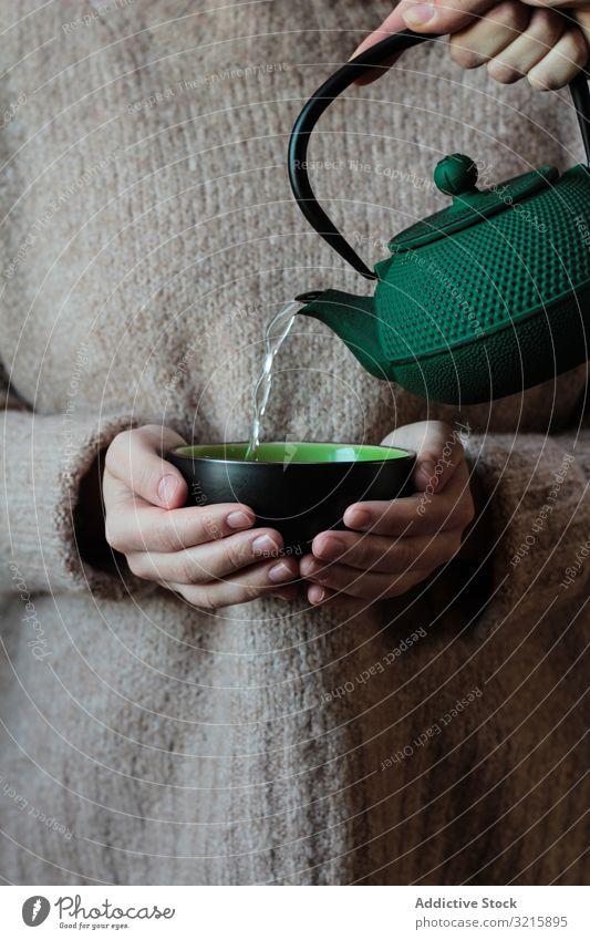Person, die in den Händen einer Frau Tee in die Tasse gießt gestrickt Teekanne Erholung Gießen trinken Hand heiß Getränk Pullover eingießen Wasser Wasserkessel