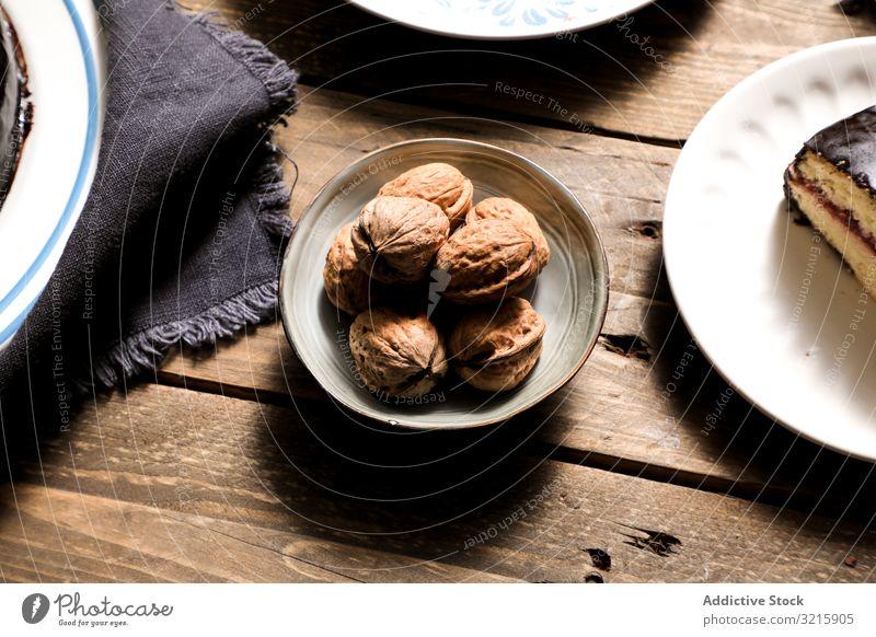 Nüsse in Schalenkuchen und Serviette auf dem Tisch Muttern Kuchen Stoff Dessert selbstgemacht Lebensmittel Bäckerei Essen zubereiten süß braun ungeschält