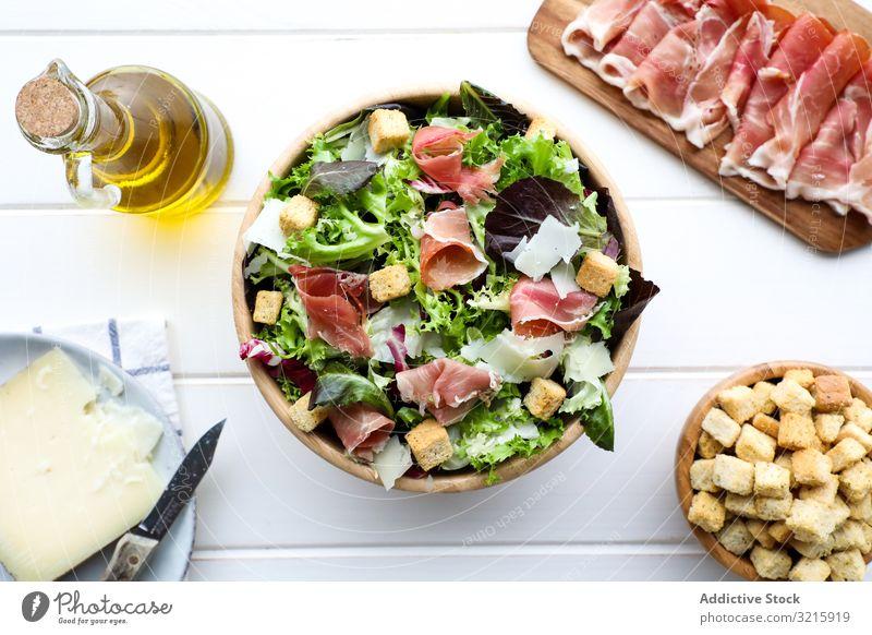 Leckerer Salat mit Speck und Croûtons Salatbeilage Schalen & Schüsseln Tisch Croutons Erdöl Käse Messer Lebensmittel vorbereitet lecker geschmackvoll köstlich