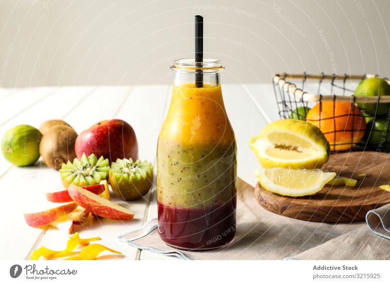 Flasche mit geschichtetem Smoothie Frucht Schichten Stroh Gesundheit Tisch sortiert mischen süß Lebensmittel Diät frisch organisch Glas Dessert Kiwi Apfel