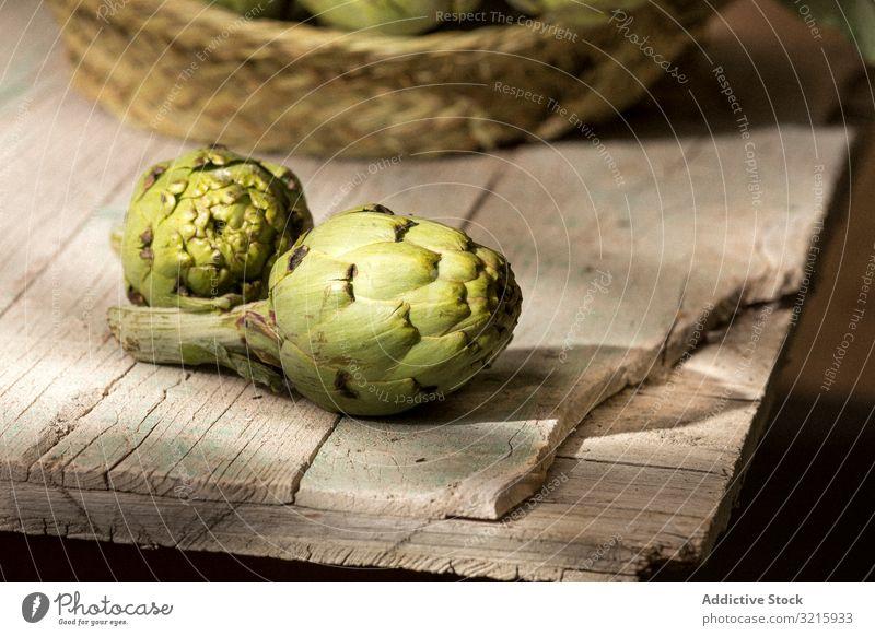Grüne Artischocke auf Holztisch grün frisch Gemüse Lebensmittel Gesundheit roh Vegetarier Bestandteil ganz organisch essen Ackerbau Ernährung essbar lecker reif