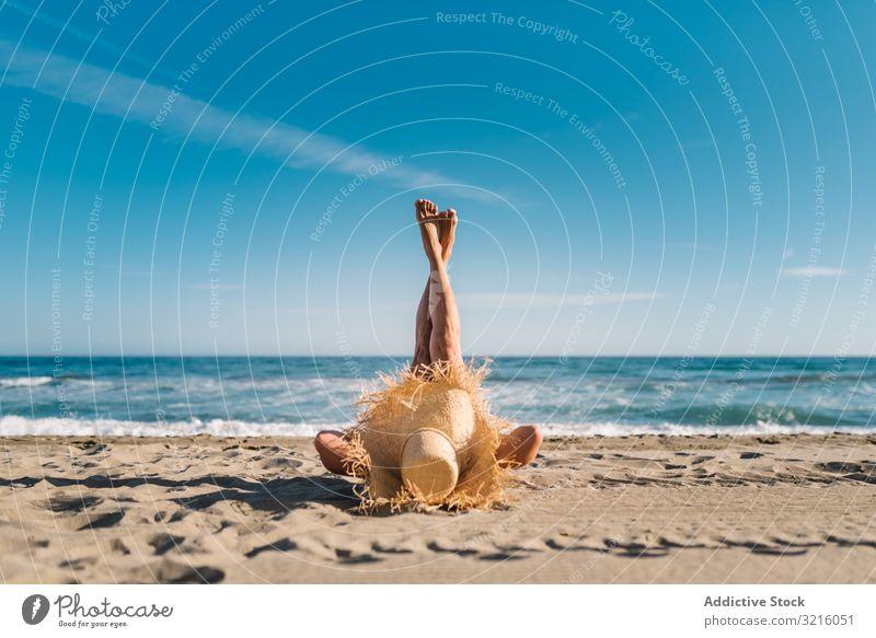 Frau mit großem Hut am Sandstrand liegend schlank Bräune Strand sandig Wasser attraktiv Sommer Freizeit sportlich Tierhaut Körper Seeküste wellig bedeckt