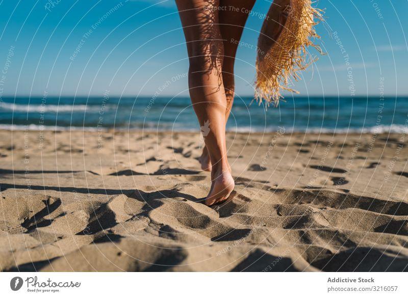Frauenbeine am Sandstrand Ernte Strand anonym unkenntlich horizontal Rückansicht sandig Badebekleidung Hut Wasser laufen Meer Sommer genießend Freizeit Körper