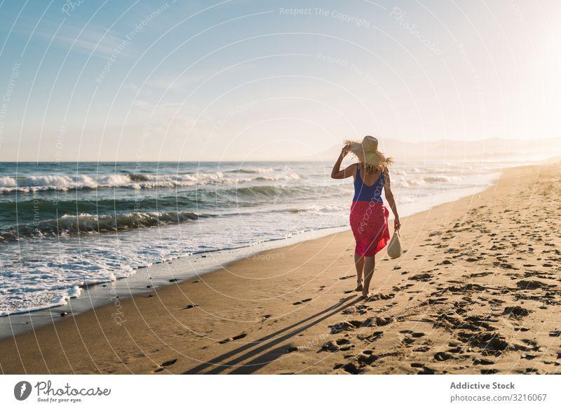 Frau hält Hut und geht am Meer entlang Strand sandig Badebekleidung pareo Wasser laufen Sommer genießend Freizeit sportlich Körper Glück schlank Seeküste wellig