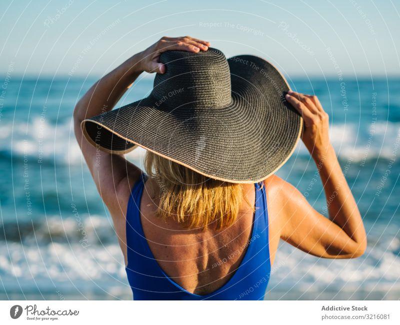 Frau in blauem Badeanzug und Hut am Sandstrand schlank Strand schäumen sandig Badebekleidung winken Wasser Sommer Freizeit Bräune attraktiv Seeküste bedeckt