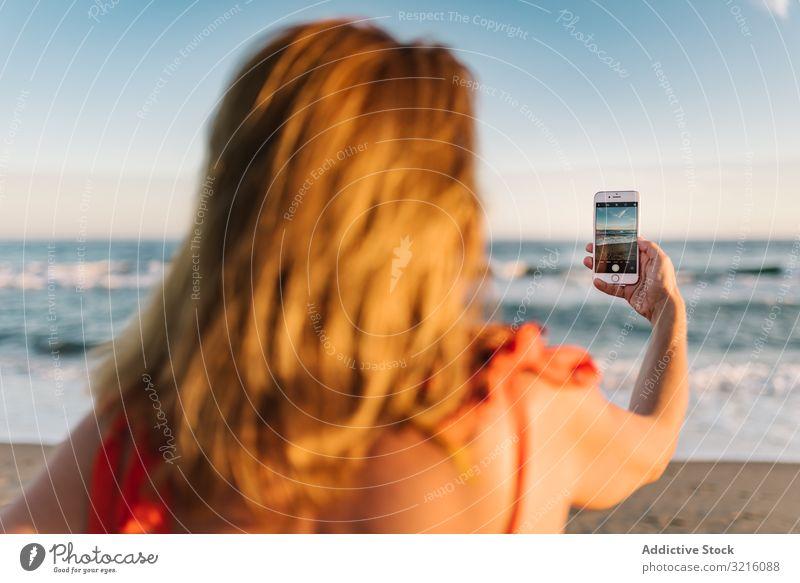 Frau in rotem Kleid fotografiert mit Smartphone Handy Fotografie Strand sandig Wasser Mitteilung Gerät Sommer benutzend Bild Freizeit Apparatur attraktiv