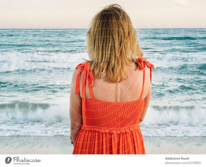 Frau in rotem Kleid schaut am Meer entlang Strand sandig Wasser Wellen nachdenklich genießend Sommer entspannend Freizeit Meereslandschaft Lifestyle Urlaub