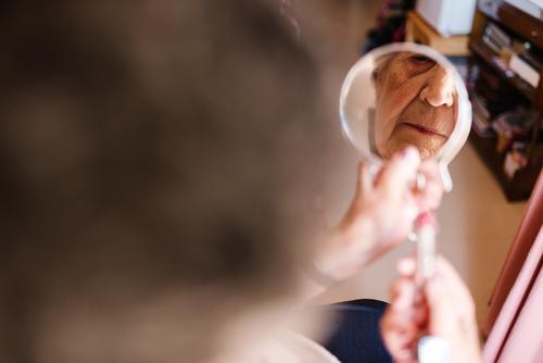 Ältere Frau schminkt ihre Lippen zu Hause gealtert Großmutter Make-up heimwärts Erfahrung Weisheit Pflege Schönheit Senior älter Hautfalten Oma grauhaarig