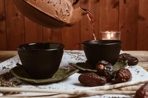Aromatische Teedatteln und Ton-Teekanne auf dem Tisch Daten Blätter Kräuterbuch trinken grün heiß natürlich traditionell Getränk Schalen & Schüsseln