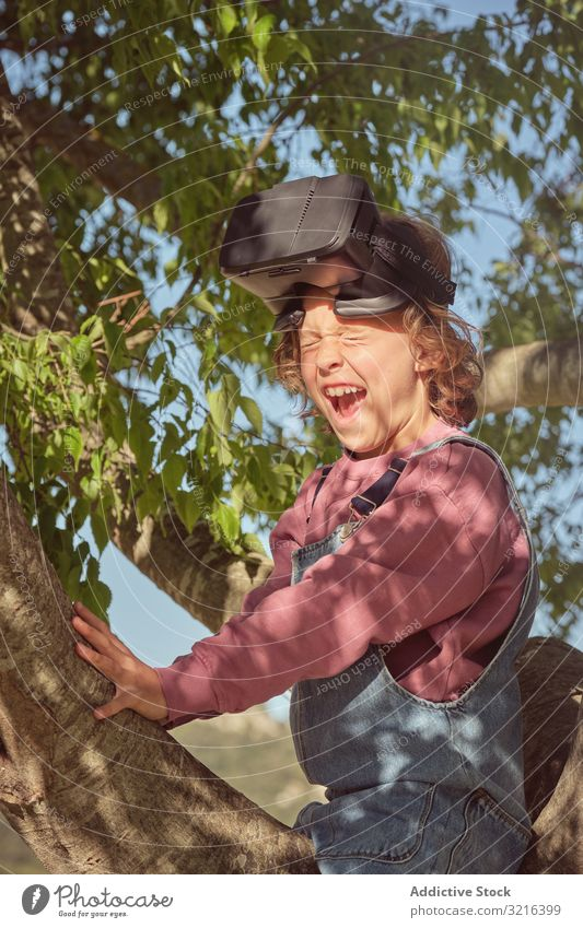 Junge in Virtual-Reality-Brille im Baum sitzend Virtuelle Realität freudig Sitzen Glück Kind wenig heiter Kindheit Spaß Lächeln zuschauend lässig Natur Sommer