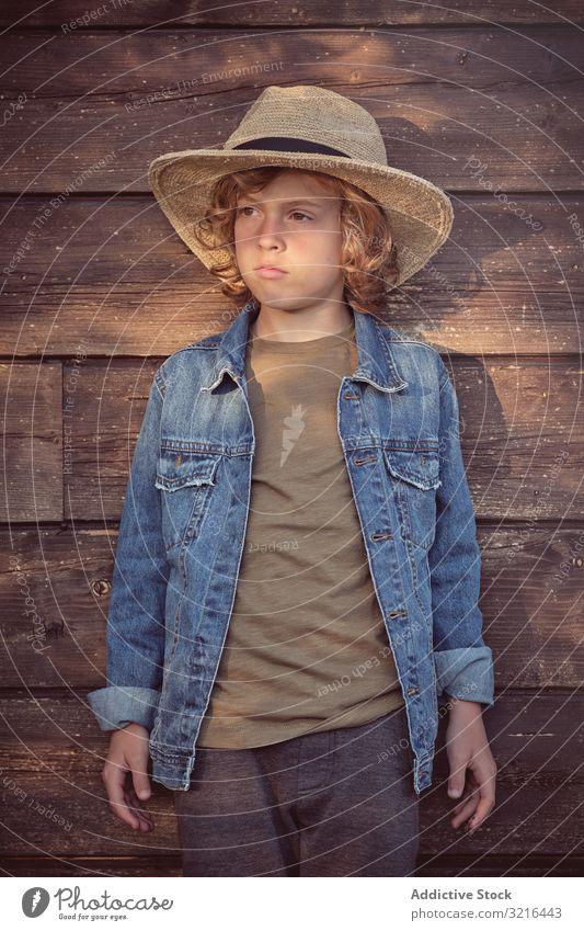 Kleiner Junge steht neben Holzhütte Stehen Kind wenig Spaß lässig Sommer lustig aktiv Freiheit bezaubernd unschuldig Feiertage Kindheit fröhlich Lifestyle