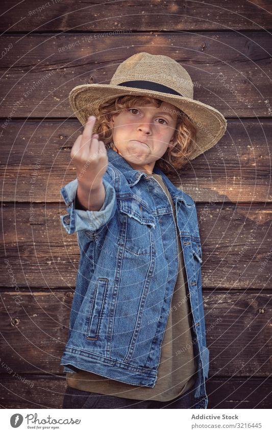 Frecher selbstbewusster Junge gestikuliert Fick dich gestikulierend Stehen Kind wenig Mitte Finger obszön zeigend Spaß lässig Sommer lustig aktiv Freiheit Hand