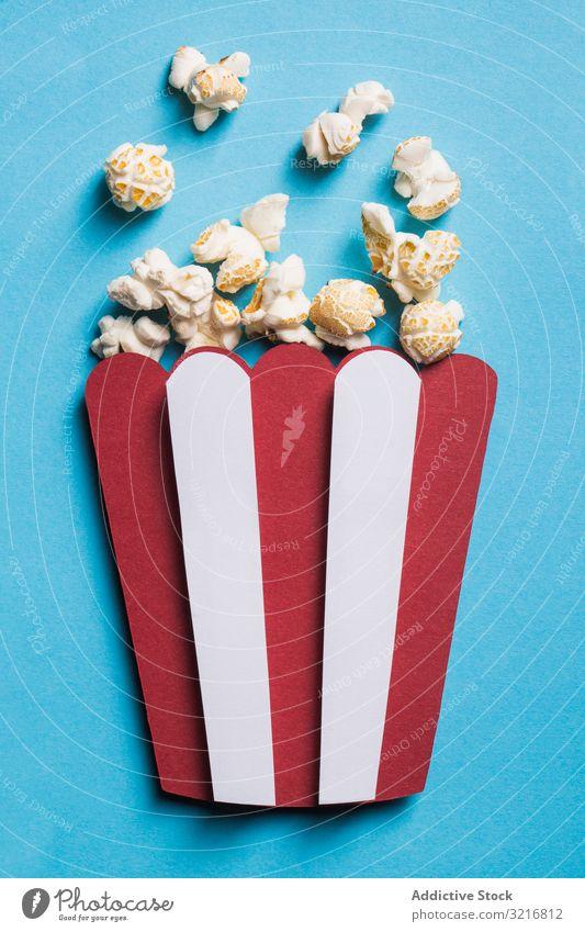 Silhouette einer Popcornschachtel aus Karton mit echtem Popcorn Kunst Kasten Kino Collage farbenfroh Zusammensetzung Konzept konzeptionell Handwerk Kreativität