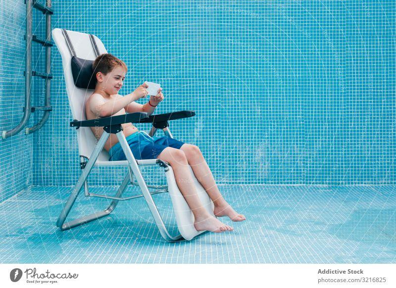 Junge mit Smartphone auf dem Boden eines leeren Schwimmbeckens sitzend Pool Sitzen Gesäß Kind aussruhen Stuhl Fliesen u. Kacheln dekoriert Technik & Technologie