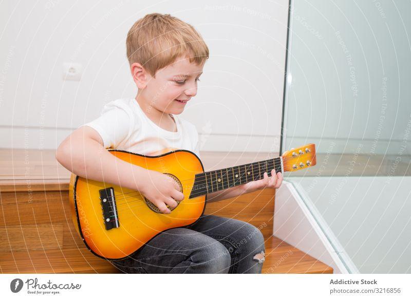 Junger blonder Junge spielt Spielzeuggitarre Gitarre Spielen Musik Instrument Kind Hobby Musiker talentiert wenig männlich lässig niedlich bezaubernd