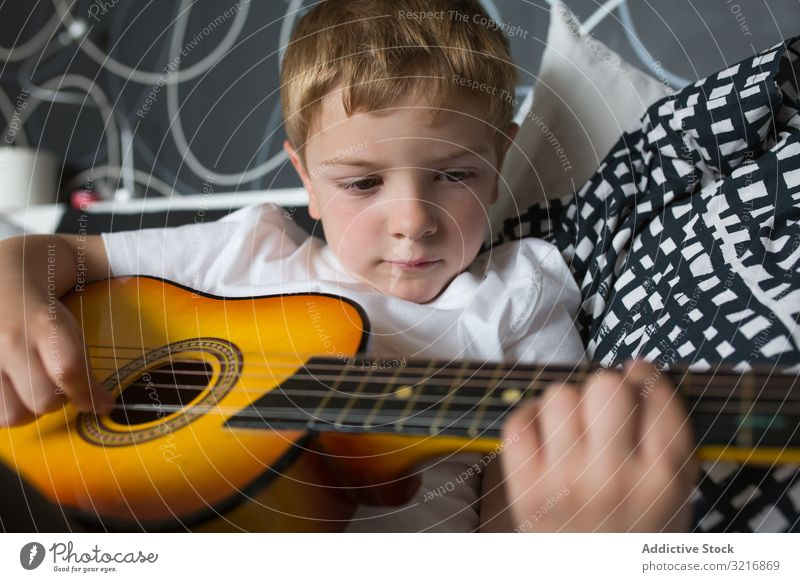 Junger blonder Junge spielt Spielzeuggitarre Gitarre Spielen Musik Instrument Kind Hobby Musiker talentiert wenig männlich Person lässig niedlich bezaubernd