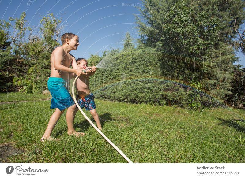 Kleine Kinder in Badebekleidung haben Spaß mit Spritzwasser Geplätscher Wasser Sommer Spielen Glück Beteiligung Lifestyle Freizeit Erholung Feiertag Kindheit