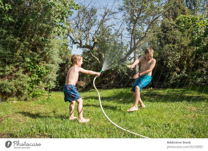 Kleine Kinder in Badebekleidung haben Spaß mit Spritzwasser Geplätscher Wasser Sommer Spielen Glück Lifestyle Freizeit Erholung Feiertag Kindheit Freude Genuss