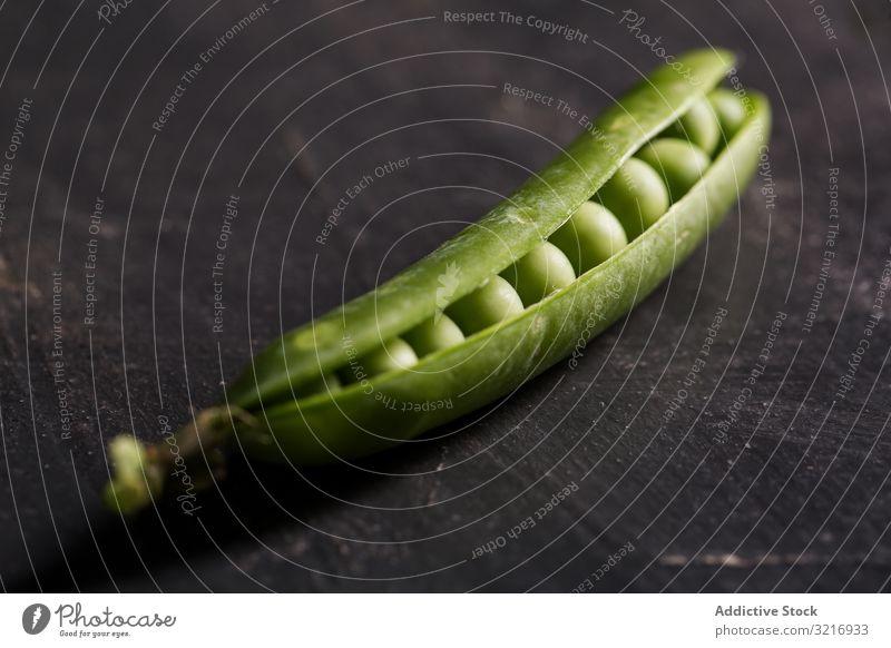 Frische Erbsen und Erbsenschoten auf dunklem Hintergrund ökologisch Lebensmittel frisch grün Gesundheit Hülsenfrüchtler natürlich organisch roh Samen Gemüse