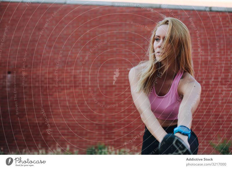 Frau dehnt sich nach dem Laufen aktiv sportlich schön blond Körper Herz Wellness Kaukasier Übung Fitness Fitnessstudio Gesundheit joggen Lifestyle im Freien