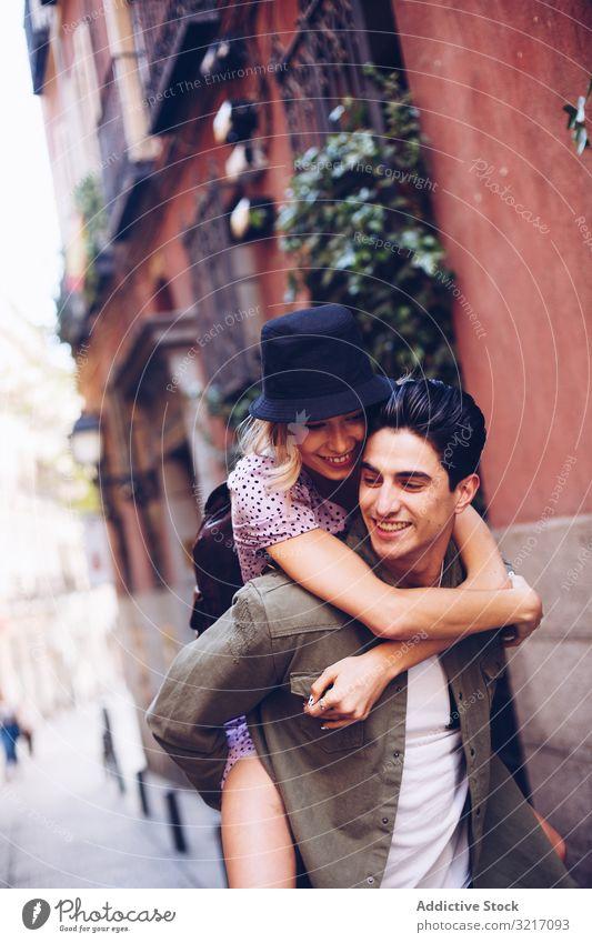Glückliches Paar amüsiert sich beim Spaziergang in der Stadt Spaß haben laufen jung Huckepack heiter Frau Mann Freizeitbekleidung Datierung genießend Freundin