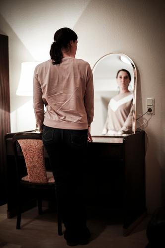Frau im Spiegel Mensch Einsamkeit dunkel Lifestyle Erwachsene Leben feminin Gefühle Stimmung Häusliches Leben Wohnung Raum Körper nachdenklich 45-60 Jahre