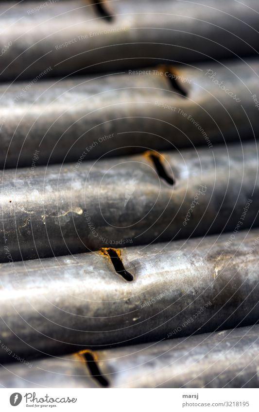 Verzinkte Eisenrohre mit Schlitzen Rost verzinkt Außenaufnahme abgenutzt aussortiert parallel Schwache Tiefenschärfe eingedrückt Schrott
