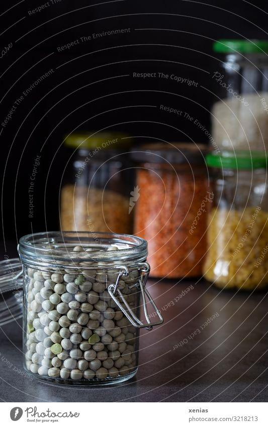 abgefüllte Erbsen in offenem Glasbehälter vor weiteren Vorratsgläsern Einmachglas Nudeln Linsen Bioprodukte kaufen modern retro Lebensmittel nachhaltig