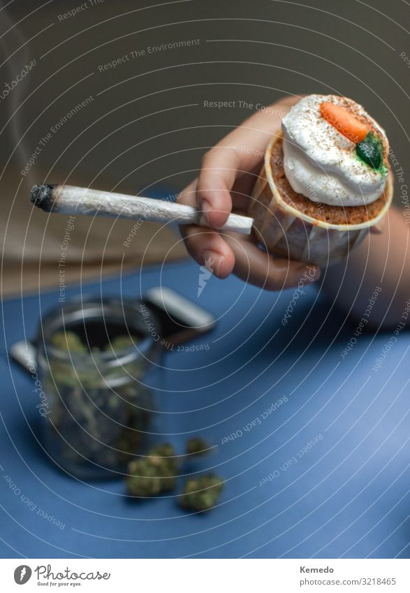 Hand mit einem Joint aus Marihuana und Kuchen aus Cannabis. Süßwaren Frühstück Lifestyle Freude Alternativmedizin Übergewicht Rauchen Rauschmittel Wellness