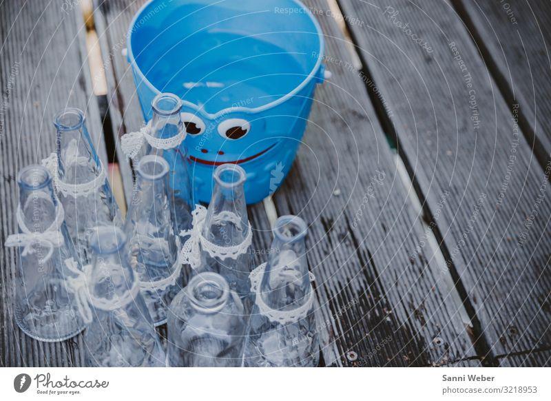 Blauer Eimer mit Gesicht Kunststoff Glück Glas Flasche Schleifenband weiß Holz Bodenbelag nass Farbfoto mehrfarbig Außenaufnahme Nahaufnahme Textfreiraum rechts