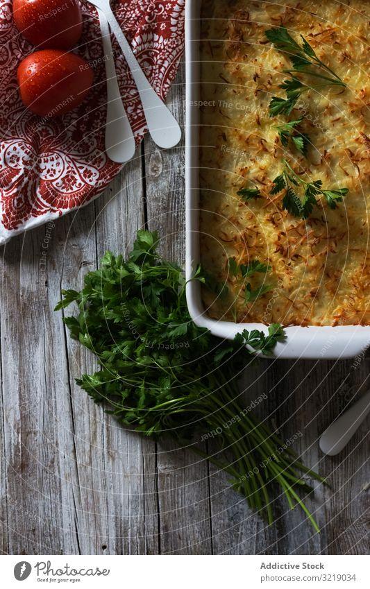 Käsegericht mit Kräutern Speise Kraut Tomate Petersilie Pfanne gebraten Tisch rustikal Serviette hölzern Mahlzeit Lebensmittel Küche lecker geschmackvoll