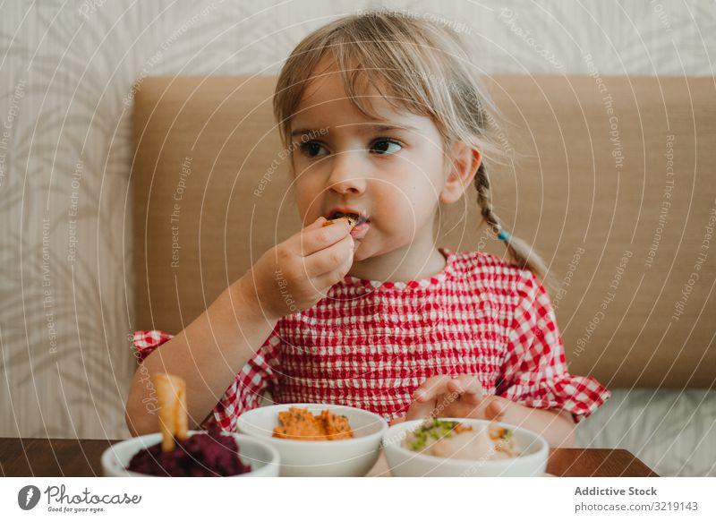 Mädchen isst mit handverlesenem Essen am Tisch Schalen & Schüsseln Feinschmecker selbstgemacht organisch Ernährung geschmackvoll erfrischend roh bezaubernd