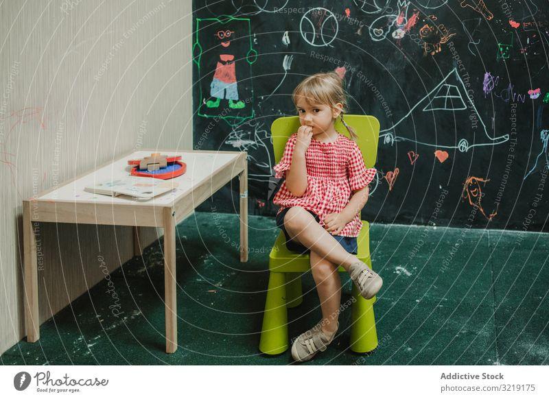 Mädchen sitzend auf hellgrünem Stuhl mit gekreuzten Beinen Kind bezaubernd Kindheit kreativ wenig Kreativität Bildung Spaß Lernen spielen Glück niedlich
