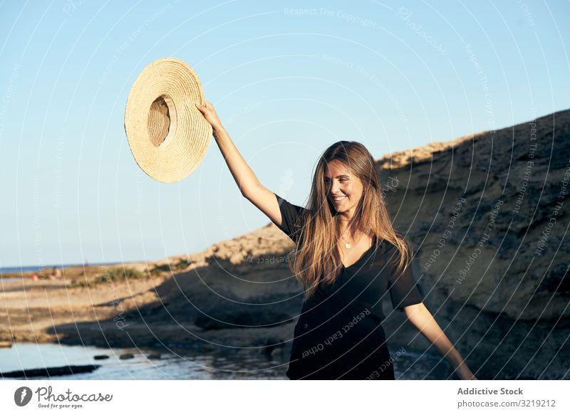 Fröhliche Frau hält Hut in der Luft Model heiter Strand Natur Lächeln stylisch jung attraktiv schön hübsch Sommer natürlich elegant posierend reisen Tourist