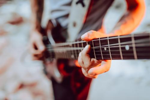 Mann spannt Saiten am Gitarrenhals ein Musiker elektrisch Hals Schnur Verschluss Leistung Griffbrett Instrument Entertainment spielen männlich Klang Felsen live