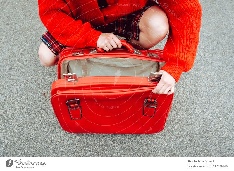 Frau öffnet Koffer auf der Straße rot reisen stylisch Gepäck Tierhaut schön Tasche Freiheit allein urban Ausflug Reise Buchse Genuss Vergnügen Model Tourist